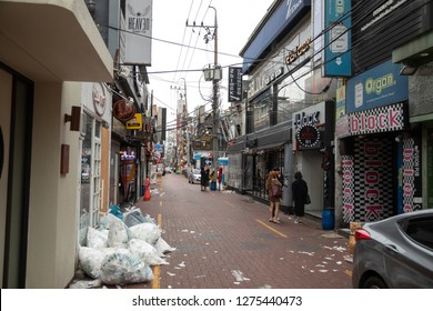 Janggwan-Dong, Daegu, South Korea - October 9 2018: Alley lined by karaoke bars and clubs in downtown Daegu, with street littered with trash and garbage bags