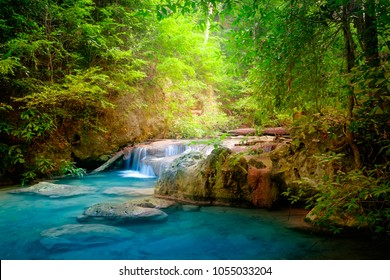 Jangle landscape with flowing turquoise water of Erawan cascade waterfall at deep tropical rain forest.Park Kanchanaburi, Thailand