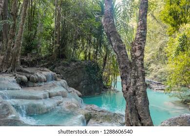 Jangle landscape with flowing turquoise water of Erawan cascade waterfall at deep tropical rain forest. Park Kanchanaburi, Thailand