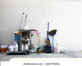 Janitor cart with equipment or tools for cleaning service in office, department store, factory and company. Cleaning cart with brooms, mop, swab, bucket, floor Cleaner in empty space background.