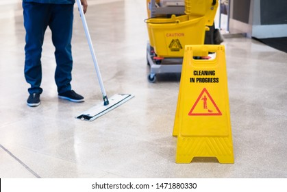 "Janitor Cleaning Floor In Front Of Yellow Caution ""Cleaning in progress"". Cleaning service in public area."