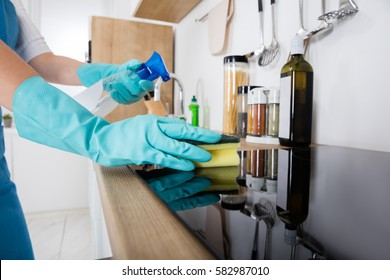 Janitor Cleaning Kitchen Worktop With Sponge And Spray Bottle