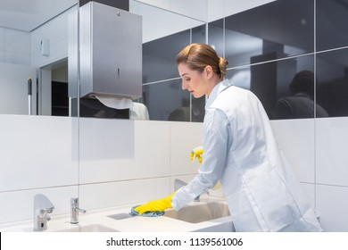 Janitor cleaning sink in public washroom with cloth