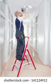 Janitor in Coverall Repairing Broken Light