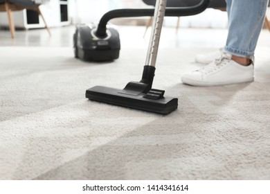 Janitor hoovering carpet with vacuum cleaner indoors, closeup