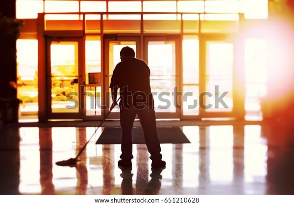 Janitor zermürbt einen Büroboden, flacher Fokus, Kippbild