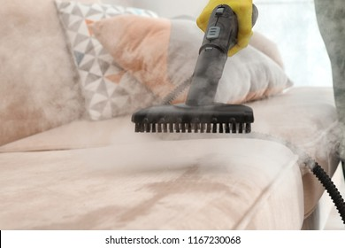 Janitor removing dirt from sofa with steam cleaner, closeup