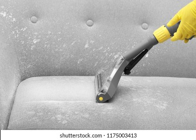 Janitor removing dirt from sofa with upholstery cleaner, closeup
