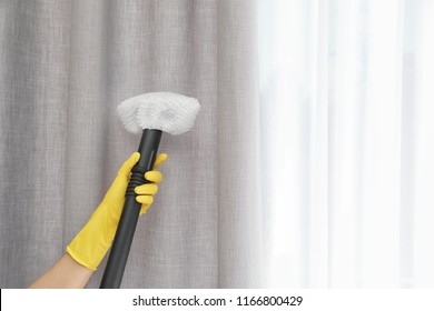 Janitor removing dust from curtain with steam cleaner indoors, closeup