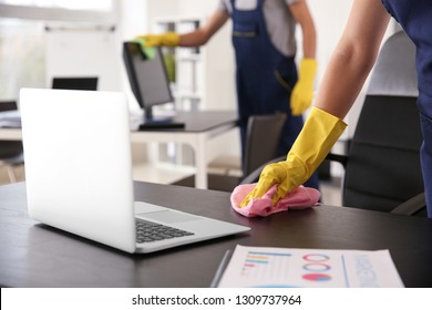 Janitor wiping table in office