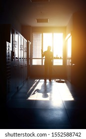Janitor woman mopping floor in hallway office building or walkway after school or classroom in the dark. Silhouette housekeeper working at evening time with sun light background.