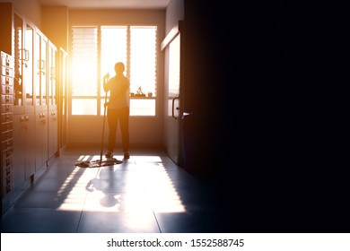 Janitor woman mopping floor in hallway office building or walkway after school or classroom with blank copy space. Silhouette housekeeper working job with sun light background.