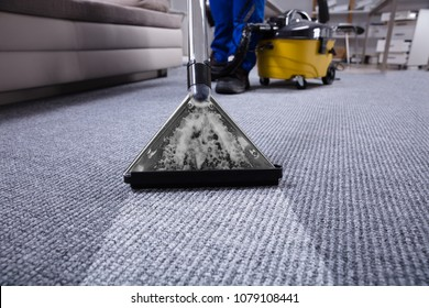 Janitor's Hand Cleaning Carpet With Vacuum Cleaner