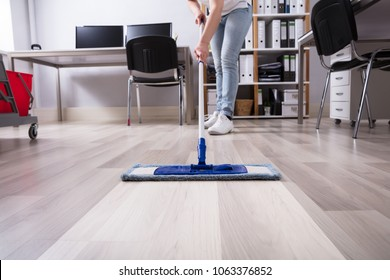 Janitor's Hand Cleaning Floor With Mop At Workplace