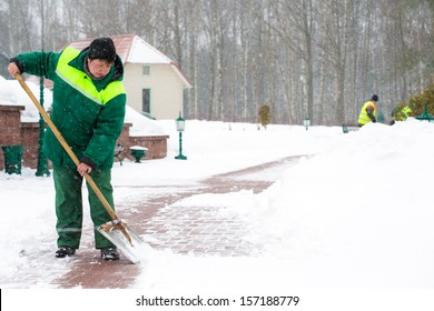 Janitors workers in uniform shoveling snow after a storm