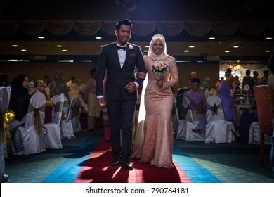 January 1, 2018 - Kuala Lumpur, Malaysia : the handsome groom and beautiful bride walk to the beautiful wedding dais during Malay wedding photoshoot in Malaysia. Image is soft