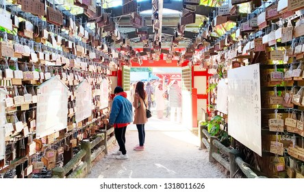 January 1, 2019 - Miyazaki, Japan :: A couple stand in a Tunnel of Pray at Aoshima Shrine, peoples make a pray by write on a mini wooden board and hang it on this pentagon tunnel