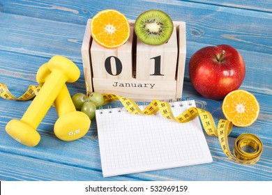 January 1 on cube calendar, fresh fruits, dumbbells and tape measure, new years resolutions of healthy lifestyle