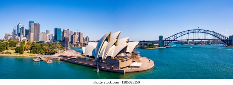 January 10, 2019. Sydney, Asutralia. Aerial view of the Sydney center by the park near Sydney Opera house, harbour bridge and city downtown. Small boats going past the opera house.