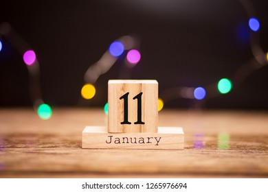 January 11th. Day 11 of month, calendar on dark background with garland bokeh. Winter time