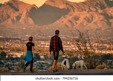 January 12, 2018 - Tucson Arizona USA - couple walking their dogs on Sentinal Peak with Catalina Mountains in the background, illuminated by the setting sun.