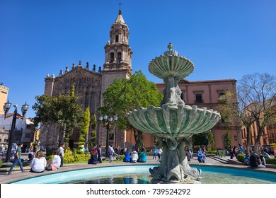 January 18, 2016 San Luis Potosi, Mexico: people sitting on rim of water fountain in front of San Luis cathedral in the colonial historic center
