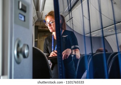 January 18 2018 United airlines flight USA; a flight attendant is seen helping  travelers in first class on an airplane  in mid flight