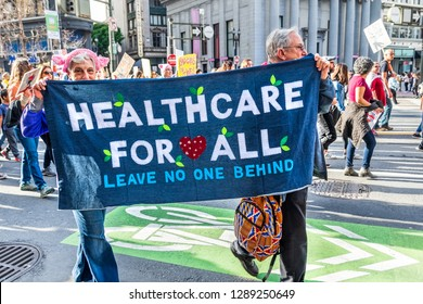 "January 19, 2019 San Francisco / CA / USA - Participants to the Women's March event carry ""Healthcare for all"" sign while marching on Market street in downtown San Francisco"