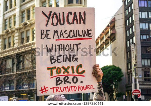 """January 19, 2019 San Francisco / CA / USA - Participant to the Women's March event holds sign referencing """"toxic masculinity"""" while marching on Market street in downtown San Francisco"""