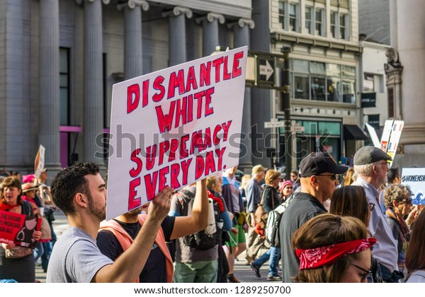 """January 19, 2019 San Francisco / CA / USA - Participant to the Women's March event holds """"Dismantle white supremacy everyday"""" sign while marching on Market street in downtown San Francisco"""