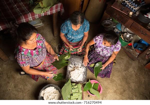 January 20, 2015 San Pedro la Laguna, Guatemala: Mayan women in traditional wear preparing food together