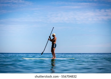 January 20, 2015. Sea of Cortez off Los Barriles, Baja California Sur, Mexico.  An African American man on a paddle board moves across the calm waters of the Sea of Cortez on a windless day.