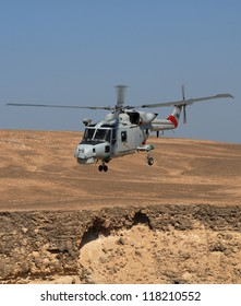 January 2009. Agusta Westland Lynx helicopter over Red Mountain, Masirah Island, Oman Blue sky and red brown rocks