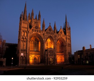 January 2012. Peterborough Cathedral, Cambridgeshire, UK seen at dusk with the frontage lit by lights and deep darkening clear blue sky.