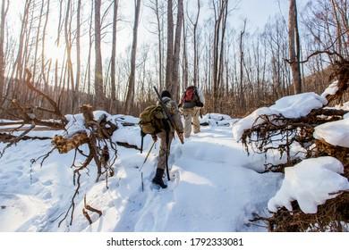January, 2016 - Agzu, Primorsky Territory - Udege hunters with guns walk through deep snow in the taiga. Wild animal hunting in Russia