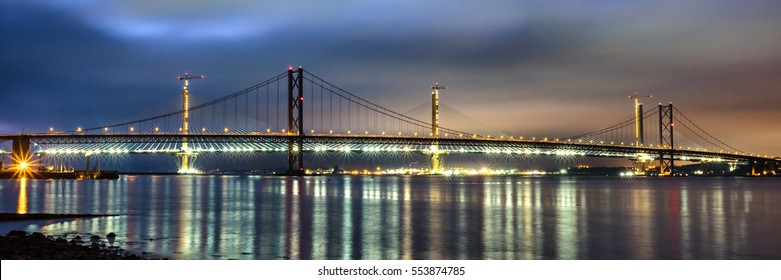 January 2017 - Panoramic night view two of the forth bridges the 'Forth Road bridge' (at the foreground) and the 'Queensferry Crossing' behind (still under construction). South Queensferry, Scotland