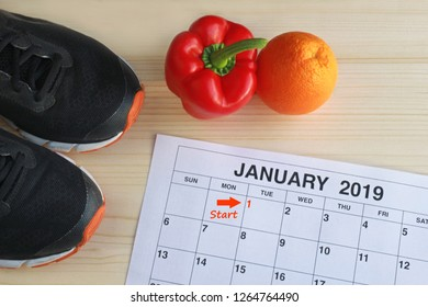 January 2019 - Start in a new healthy life, calendar page of january, jogging shoes, a red pepper and an orange on a bright wooden table