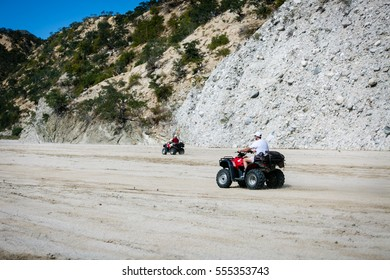 January 24, 2015.  Arroyo Buenos Aires, Baja California Sur, Mexico.  Two ATV riders race on flat sand up a dry arroyo on the southern end of the Baja Peninsula.