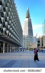 January 25 2017 - Riyadh, Saudi Arabia: A Man walks nearby the Saudi National Museum park and Al Faisaliyah Center Tower  in the background along Olaya Street area.