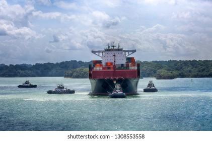 January 28, 2019, Panama Canal, Panama. Tug boats pulling large ship to enter locks of the Panama Canal