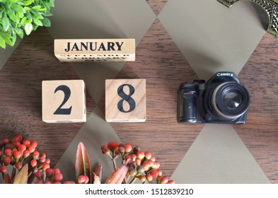 January 28, Date design with Number cube, a flower and camera on Diamond wood background.