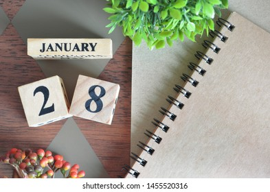 January 28. Date of January month. Number Cube with a flower and notebook on Diamond wood table for the background.