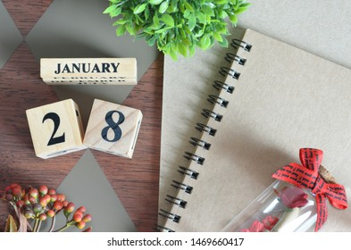 January 28. Date of January month. Number Cube with a flower, Rose bottle and notebook on Diamond wood table for the background.