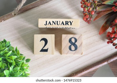 January 28. Date of January month. Number Cube with a flower and Sign wood on Diamond wood table for the background.