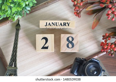 January 28. Date of January month. Number Cube with a flower camera and Sign wood on Diamond wood table for the background.
