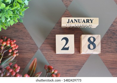 January 28. Date of January month. Number Cube with a flower and leaves on Diamond wood table for the background