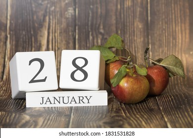 January 28. Day 28 of month. Calendar cube on wooden background with red apples, concept of business and an important event. Winter season.