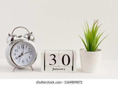 January 30 on a wooden calendar next to the alarm clock.Calendar date, holiday event or birthday.The concept of one day of the month.