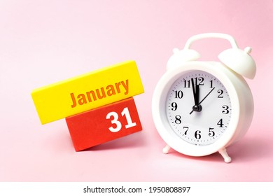 January 31st . Day 31 of month, Calendar date. White alarm clock on pastel pink background. Winter month, day of the year concept