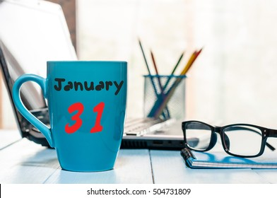 January 31st. Day 31 of month, Calendar on cup morning coffee or tea, workplace background. Winter at work concept. Empty space for text